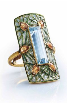 GEORGES FOUQUET - AN ART NOUVEAU AQUAMARINE, GARNET AND ENAMEL RING, CIRCA 1900. Set with a rectangular-cut aquamarine within a rectangular bombé panel of green and blue window enamel of stylised pine design, applied with six pear-shaped spessartite garnets, with French assay mark for gold, signed G. Fouquet, numbered, with maker's marks for Georges Fouquet.
