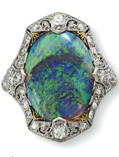 A BELLE ÉPOQUE BLACK OPAL AND DIAMOND RING Set with an oval cabochon black opal within an old European-cut diamond surround and shoulders, mounted in platinum, circa 1915