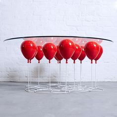 A Glass Table That Appears To Be Held Aloft By Helium Balloo...