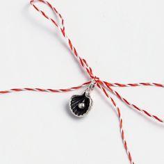 Mărțișor din argint delicat, în formă de scoică cu perlă. După luna martie, mărțișorul poate fi purtat ca un charm la mână sau la gât, pe lanț sau șnur. Cu fir clasic alb-roșu și ambalat într-o punguță cadou, mărțișorul scoică cu perlă este gata pentru a fi oferit. #metaphora #martisor #martisoare #martisorargint #martisoareargint #martisordinargint #martisoaredinargint #silvercharm