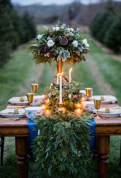 Cold-weather wedding centerpiece of wintergreens with white pine, balsam and cedar stems, seasonal berries, and pine cones