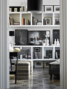 styling a bookcase, art, black and white art, black drum chandelier, ivory and black ottomans