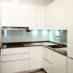 Cocina moderna blanco brillo sin tiradores  Encimera Silestone Pared forrada en cristal  Iluminación led