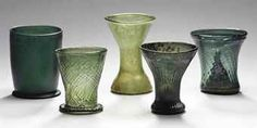 FIVE LATE MEDIEVAL WALDGLAS BEAKERS  15TH-17TH CENTURY, GERMANY  Three of wrythen-moulded tapering form, one with a folded foot, the fourth plain, waisted, the fifth of plain wide form applied with a single coil footrim The largest 4 1/8 in. (10.4 cm.) high (5)