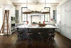 Cozinha com bancada em ilha com tampo branco e base preta, banquetas antigas com encosto, piso de madeira, armários da cozinha cinza, lustre, luminárias pendente antigas. Inspirações e Dicas de Decoração Para Cozinha Industrial