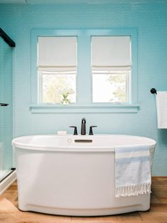 Privately connected to the master bedroom and with an attached closet, the master bath takes a bright turn with an allover brilliant blue palette, including wall color and matching penny tile. With both a shower and freestanding tub, the bath space provides ample opportunities to relax.