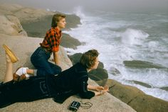 National Geographic Found- Two women gaze at heavy surf while lying on boulders on the coast of Nova Scotia, December 1961. Photograph by Volkmar Wentzel, National Geographic.