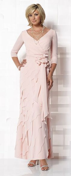 Mock wrap chiffon A-line dress with three-quarter length sleeves, front and back V-necklines, ruched natural waistband with removable hand-crafted flower accent and cascading streamers, diagonally tiered and scalloped skirt.