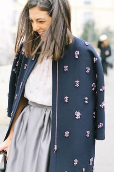 Grey skirt, white embellished shirt, navy embellished jacket, red nail polish
