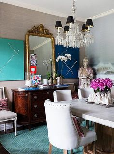 The paintings in the dining room are by Andrew Gellatly, the mirror is an Italian family heirloom, and the sideboard comes from One Kings Lane. Shop the look!