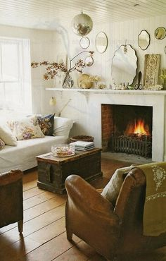 White sofa, bead board, wood, leather, trunk table, fireplace, mantle shelf, mirrors=cozy