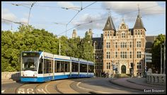AMSTERDAM - Op tramlijn 9 reed vandaag de 2106, die op de foto over de brug tussen de Maurits- en de Alexanderkade zit rijdt, op weg naar het Centraal Station.
