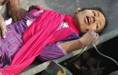 Miracle survival: The woman, named Reshma, gasped for air as she was pulled from the rubble and stretchered to safety, pictured above, after spending 17 days trapped beneath the wreckage of the factory in Bangladesh where over 1.00 people died.