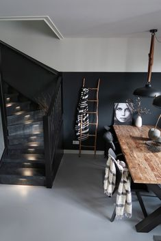 Upstairs stair renovation - Een Upstairs traprenovatie in A black staircase with dark gray paneling that continues into the k -
