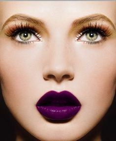 a dramatic purple lip with soft orange eyes, false lashes and groomed pale brows.