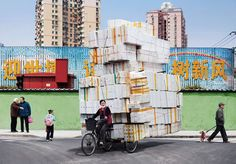 "Apparently, some people in China have never heard of U-Haul. They are, however, amazingly efficient in the way they pack and move all their inventory on a tiny little bike. ""Manufactured Totems"" is a series by Alain Delorme which brilliantly portrays the pressure Shanghainese migrant workers face. Piles of products labeled ""Made in China"" are stacked up to produce gargantuan sculptures, symbolizing their ever-increasing fetish with objects. The vertical nature of these items echoes the…"