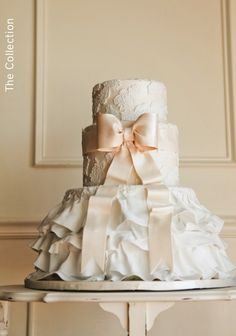 Blush wedding cake made to look like bride's gown with lace, satin bow, and ruffled skirt in fondant. View more Nashville wedding cake bakery designs by @frostedaffair2! | The Pink Bride® www.thepinkbride.com