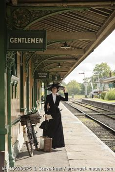 Lady in black with big hat waits on railway station with suitcase Photographer: Steve Peet