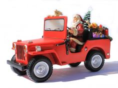 """Santa Jeep Music Box This Roman exclusive musical figurine is a fun addition to any holiday room décor. The red jeep driven by Santa is loaded with toys and a Christmas tree, with headlights that light up and music that plays various Christmas favorites. Great for Santa collectors and musical collectors. Requires batteries (not included). Size: 6""""H x 9 1/8""""W x 3 3/4""""D"""