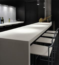 Minimal interior, clean kitchen area with white Corian table and sleek chairs _