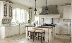 White cabinets, glass door, arched window, range hood. Avondale Custom Homes