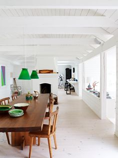 white walls, white brick, warm wood banquet-size table, open beam ceiling, lots of light and perfect Kelly green pendants