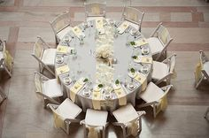 nice bird's eye view of a round table setting - Picture dark green tablecloth with light green napkins, white chair covers with light green sash and purple and green cymbidium orchid centerpiece