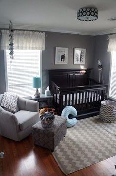 A gray and aqua nursery with a rich dark wood crib, chevron accessories, and a cozy armchair and ottoman for mom or dad to curl up in during a late night feeding.