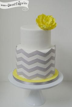2 tier cake with a taller tier of gray chevrons on a bright yellow board with a matching yellow sugar flower