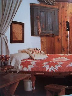 AN ANTIQUE ROPE BED WITH QUILT, A FRAMED SAMPLER, AND A HANGING CORNER CUPBOARD IN BLUE CHIPPY PAINT.