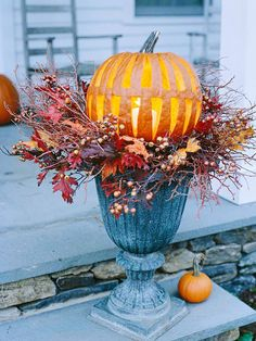 Lantern Pumpkin  Make a natural luminaria for the front step by carving long triangles into a pumpkin. A candle or LED light resting inside the pumpkin gives the look of a Chinese lantern. Rest the pumpkin in a ceramic garden urn decorated with fall leaves and berry vines.