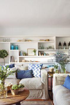 0723. Sofás con cojines azules y beige con diferentes estampados y estanterías al fondo