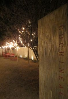 cochineal restaurant - marfa, texas  love the restaurant sign. lights in trees. neutral landscape with pops of red in chairs.