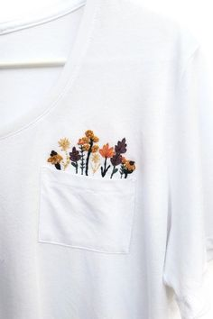 Dress up your favorite t-shirt with some DIY hand-embroidery. Perfect for beginners and advanced embroiderers alike, this digital embroidery pattern gives you all the instructions, tips, and tricks to embroider your very own t-shirt. Embroidery Bags, Embroidery Fashion, Hand Embroidery Designs, Embroidery Patterns, T Shirt Embroidery, Indian Embroidery, Folk Embroidery, Hand Embroidery Stitches, Embroidery For Beginners