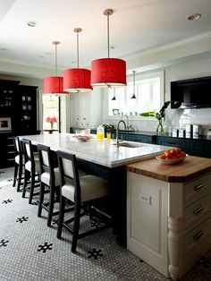 The bold red drum shades steal the show -- adding personality and drama to this kitchen. In the scheme of a kitchen remodel, pendant lights are less expensive than switching out cabinets or countertops, making them a great place to take a risk. When you need a change or grow tired of the color palette, it's an easy change.