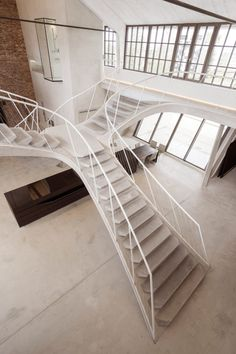 This loft apartment in a former tank station in the Austrian city of Salzburg features a sweeping concrete staircase and a glass shower cubicle that cantilevers over the living space.