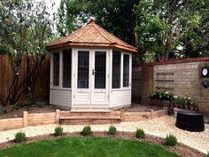 Wraysbury Octagonal cedar summerhouse painted with a cedar shingle roof. Traditional style.