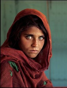 """""""Afghan Girl"""" — Sharbat Gula was only 12 years old when photographer Steve McCurry captured the young refugee in Pakistan during the 1984 Soviet occupation. A year later, National Geographic Magazine made the haunting shot its June cover. http://www.purpleclover.com/lifestyle/2211-icons-photo-subjects/item/afghan_girl/"""