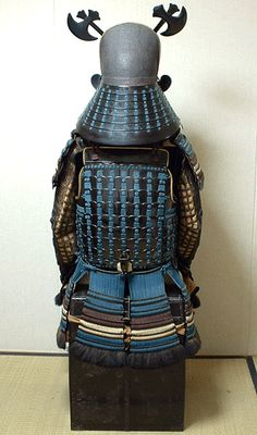 """Sumizukinnari style Kawari Kabuto with texured lacquer finish. Intricately engraved fukurin trim caps the hachi on both sides and over the top edge. A sugake odoshi laced hineno jikoro is fitted to the Kabuto and attached by 4 unsual mixed metal byo. The shikoro has 7 lames which is quite rare. The fukigaeshi have no crest which is common for a Daimyo or other high ranking Samurai. In this case dramatic masakari """"axe"""" shaped maedate is one indication of the family. It is covered in gold…"""