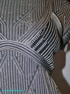Detail of stitch transfer zip dress by Rory London, 2011, NTU This close-up shows detail of a stitch transfer dress by Rory London who graduated in 2011 with a BA in Fashion Knitwear Design from Nottingham Trent University. This uses a machine knit technique called plating. Two yarns are knit at a time, but one shows on the knit side and the other on the purl side. This creates two colour ribs which are used to great effect here.