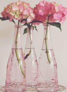"""Pretty in Pink"" - Pink hydrangeas in soft pink decorative glass bottles."