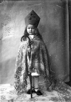 A girl dressed up as St. Nicholas with a self-made mitre and a rug as robe. The walking stick serves as crosier. The Netherlands, 1909