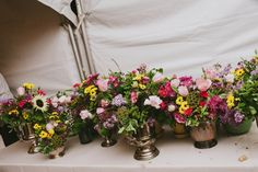 © Love Shack Photo - collection of tarnished silver pitchers and buckets used as fresh flower vases for wedding centerpieces