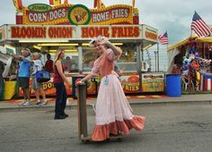 Eva Delaplane, 15, rides a wood scooter in the tractor parade onTrackside Parkway at the Indiana State Fair Wednesday August 7, 2013.