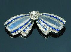 Belle Epoque platinum bow brooch by Cartier Paris, with lines of calibre sapphires, small old brilliant cut diamonds and carved moonstone panels, signed Cartier with French assay marks France, Circa 1912