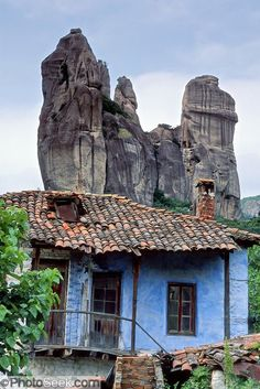 fantastic rock spires of meteora rise above a blue house with red tile roof in kastraki