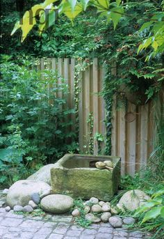 Harpur Garden Images Ltd :: gut501a Small square stone trough water feature surrounded by rocks and pebbles. Cobblestone wooden fencing boundary focal point green foliage planting Design: Ursel Gut for The Schneider Garden. Small water features Paving Fences Jerry Harpur Please read our licence terms. All digital images must be destroyed unless otherwise agreed in writing. Photograph by: www.harpurgardenlibrary.com Contact: Harpur Garden Library 44 Roxwell Road Chelmsford Essex CM1 2NB, UK