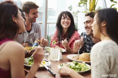 Group Of Friends Enjoying Meal At Rooftop Restaurant