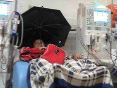 Idoso se protege de goteira com guarda-chuva em hospital