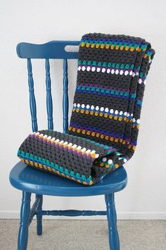 Crochet granny square blanket in grey, mustard, green, blue and purple.
